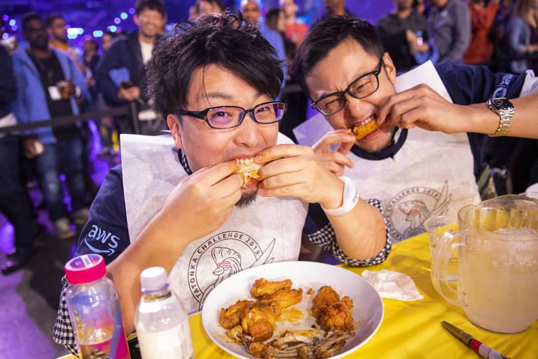 Duas pessoas parecem comendo frango enquanto olham para a câmera, com público no fundo