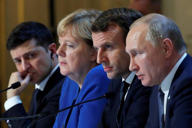 Zelenski (esq.) observa Putin (dir.) falar na entrevista após o encontro, com Merkel e Macron entre os dois