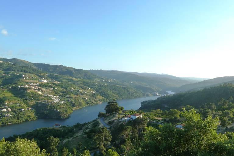Vale com pequenas vilas e casas por onde passa um rio azulado