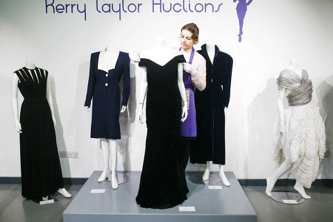 An assistant poses with Britain's Princess Diana's Victor Edelstein midnight-blue velvet evening gown (estimated at £250,000 - £350,000), which was worn by the princess when she danced with actor John Travolta at the White House in 1985. Also pictured is her Katherine Cusack evening gown (estimated at £20,000 -£30,000) and her Catherine Walker dress (estimated £4,000 - £6,000), at Kerry Taylor auctions in London, Britain December 8, 2019. REUTERS/Henry Nicholls ORG XMIT: HTN105