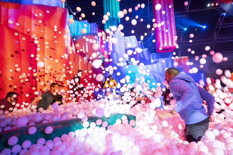Pessoas brincam jogando bolinhas para cima em piscina de bolinhas de brinquedo inflável