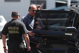 Rio de Janeiro governor Luiz Fernando Pezao is escorted by a policeman at the Federal Police headquarters in Rio de Janeiro