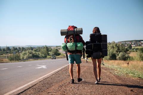 Travel man hitchhiking. Backpacker on road Foto: grthirteen / Sdobe Stock