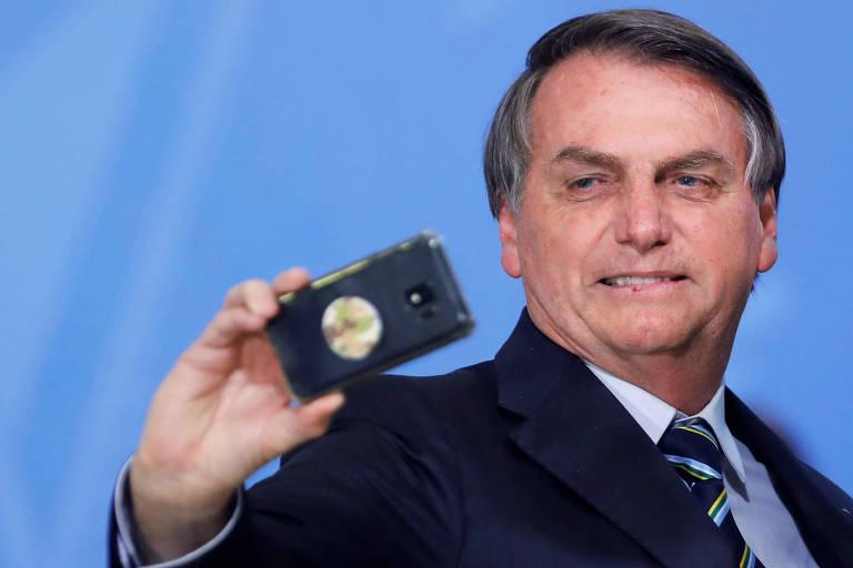 Bolsonaro tira foto com celular durante evento no Palácio do Planalto, em Brasília
