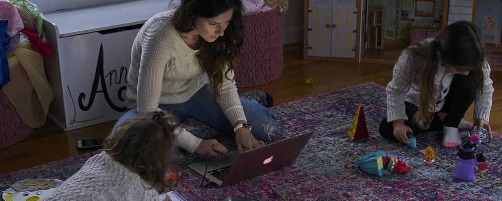 Caitlin Houston trabalha enquanto suas filhas brincam em casa, em Connecticut