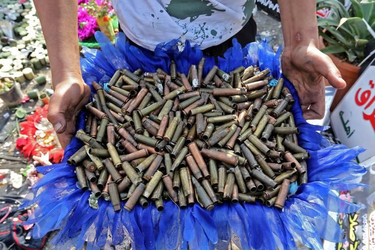 Mãos de um homem seguram uma cesta azul cheia de cartuchos de bala