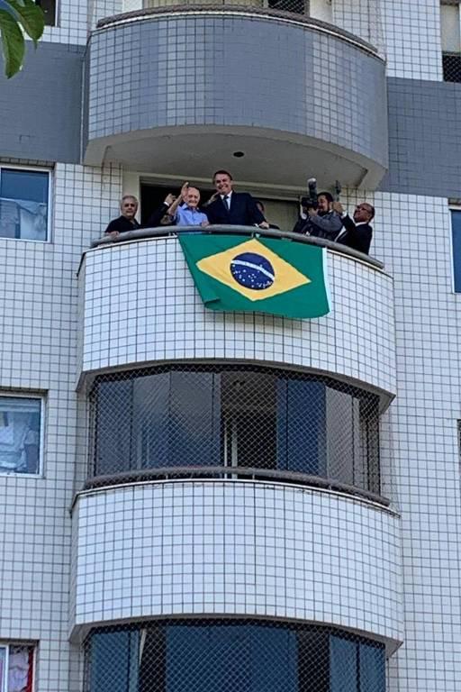 Bolsonaro está em uma sacada, onde foi estendida uma bandeira do Brasil, em meio a seis outros homens. As paredes do prédio são de pastilhas brancas.