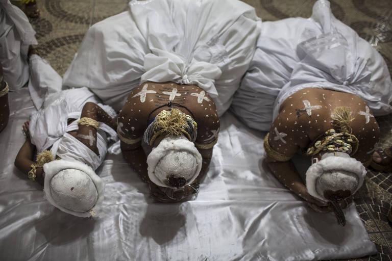 Três pessoas são vistas ajoelhadas, com o rosto no chão, usando trajes brancos ritualísticos e chapéus, com as costas pintadas com cruzes brancas, sobre um lençol