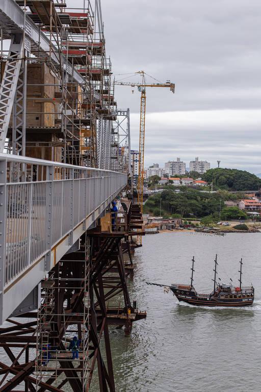 Vista lateral de ferragens de ponte pênsil com barco sob a estrutura