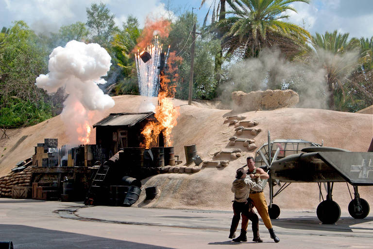 Dois homens simulam briga, enquanto carro antigo pega fogo ao fundo
