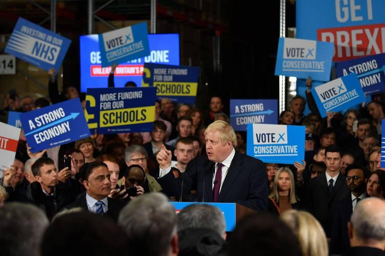 Apoiadores do primeiro-ministro e líder do Partido Conservador, Boris Johnson, carregam cartazes pedindo mais investimentos em escolas e no sistema de saúde pública britânico;