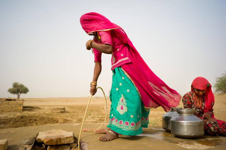 Mulheres coletam água em poço no deserto de Thar, no Rajastão, região noroeste da Índia