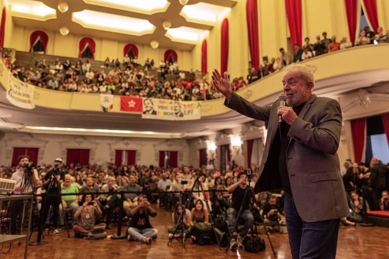 Lula segura o microfone e tem o braço direito erguido; ao fundo, vê-se um auditório de dois andares com pessoas assistindo ao discurso