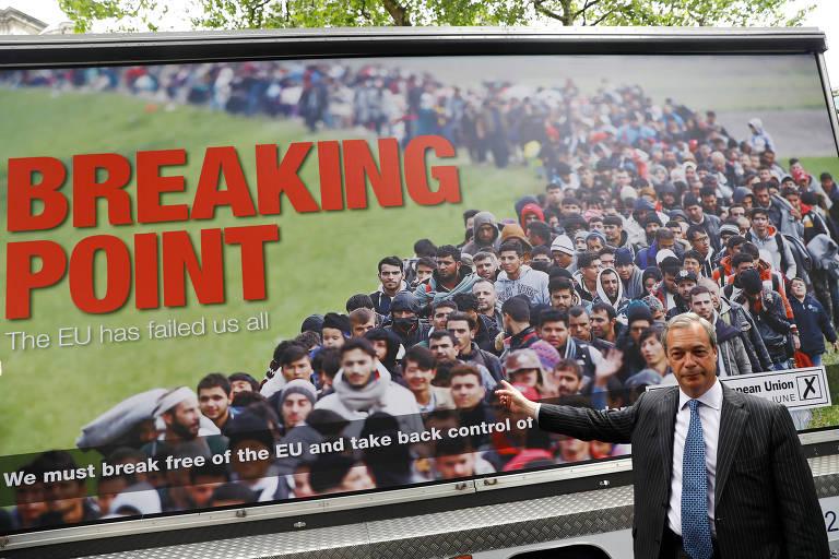 Nigel Farageposa em frente a cartaz com mensagem anti-imigração