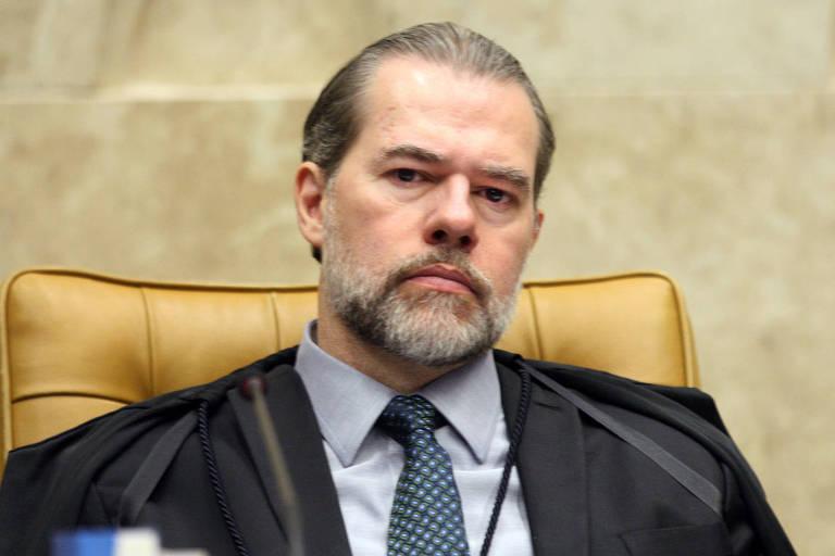 O ministro Dias Toffoli aparece sentado com o semblante sério em uma cadeira amarela no Supremo Tribunal Federal