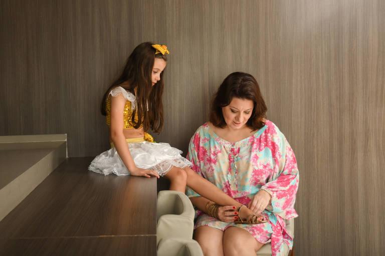 Mãe com vestido florido está sentada com os pés da filha no colo enquanto calça uma sandália nela. A menina usa laço nos cabelos e tem longos cabelos pretos