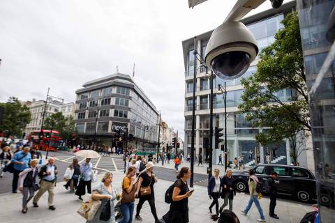 (FILES) In this file photo taken on August 16, 2019 People walk past a CCTV camera operating on Oxford Street in Londo. - The experiment was conducted discreetly. Between 2016 and 2018, two surveillance cameras were installed in the Kings Cross area of London to analyse and track passers-by using facial recognition technology. (Photo by Tolga Akmen / AFP)