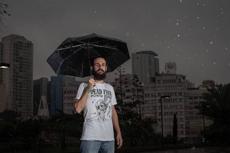 Homem com barba e camiseta branca segura guarda-chuva