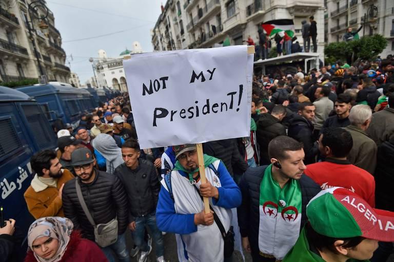 """Protesto em Argel após o anúncio da eleição de Abdelmadjid Tebboune; cartaz diz """"Não é meu presidente"""""""