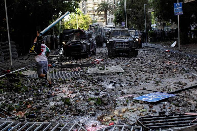 Manifestante atira bastão em direção a veículos da polícia durante protesto em Santiago, no Chile