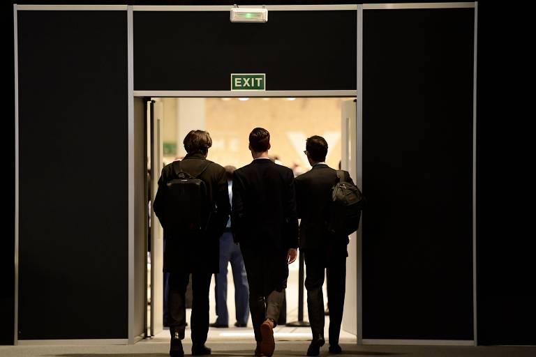 Pessoas deixam sala de reuniões
