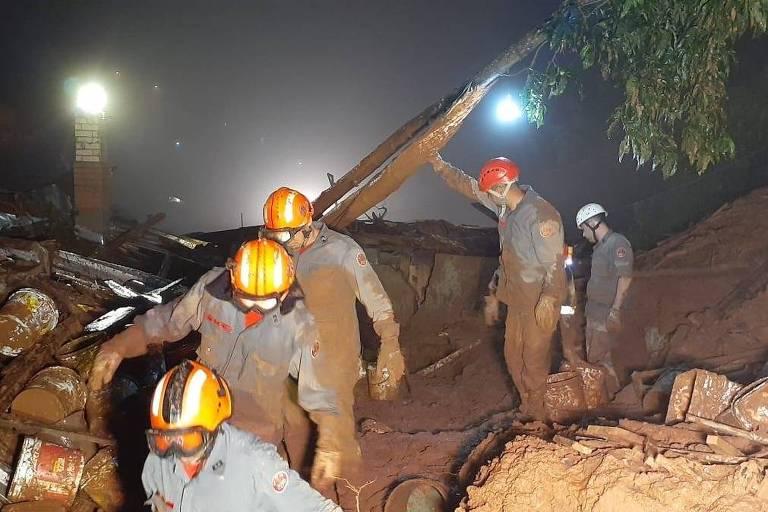 Equipes usando capacete e equipamento de proteção trabalham em meio a escombros após deslizamento de terra