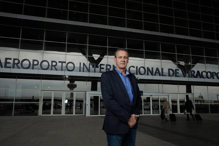 O presidente da Aeroportos Brasil Viracopos está parado em frente ao Aeroporto Internacional de Viracopos, vestindo um terno escuro com uma camisa azul por baixo. As mãos estão junta à frente do corpo e a expressão dele é séria para a câmera.