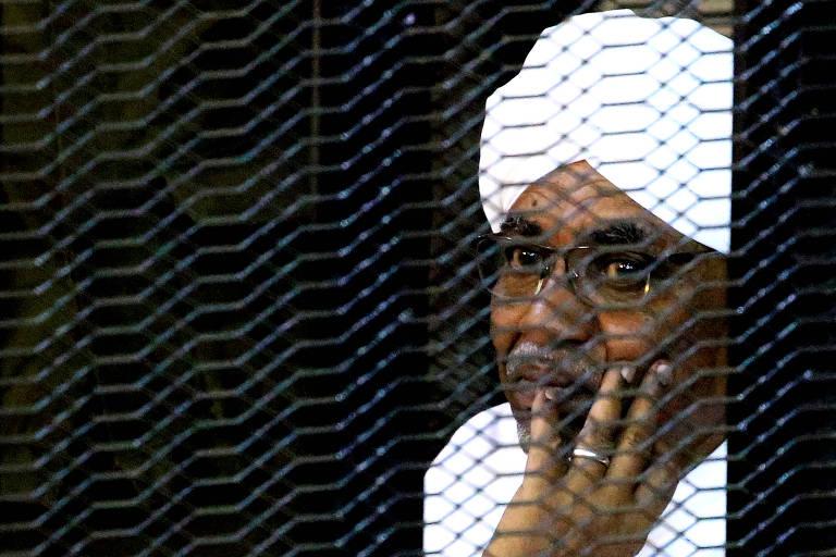 O ex-ditador sudanês Omar Hassan al-Bashir sentado dentro de uma gaiola durante julgamento que o condenou por corrupção, em , no Sudão