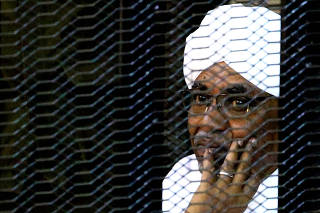 FILE PHOTO: Sudanese former president Omar Hassan al-Bashir sits inside a cage as he faces corruption charges in a court in Khartoum
