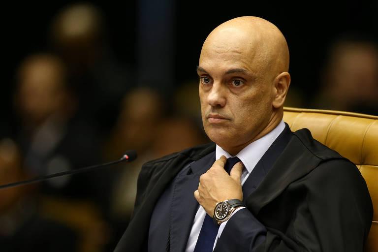 Ministro do STF, Alexandre de Moraes, aparece sentado e arrumando a gravata