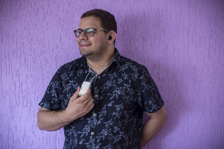 O engenheiro civil Thierry Cintra Marcondes, 32, que tem perda auditiva profunda, está sorrindo olhando para o lado e segurando com uma das mãos o aparelho auditivo pendurado no pescoço.