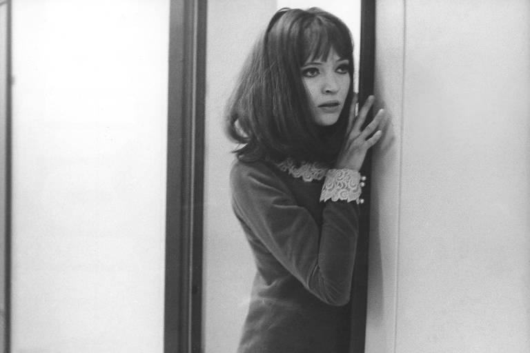Imagem em preto e branco. Ana Karina, apoiada no batente de uma porta, vestida com camiseta de manga comprida, olha para o lado.