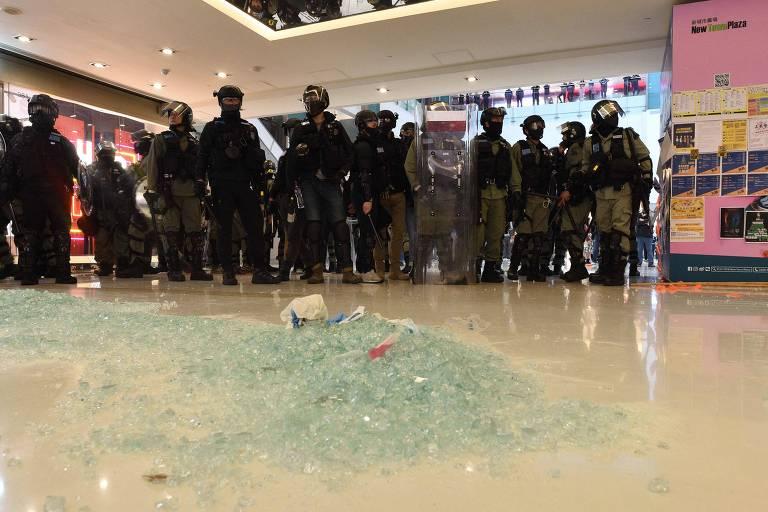 em primeiro plano, um amontoado de vidro estilhaçado no chão de um shopping. Ao fundo estão policiais, que parecem fazer uma barreira para isolar a área