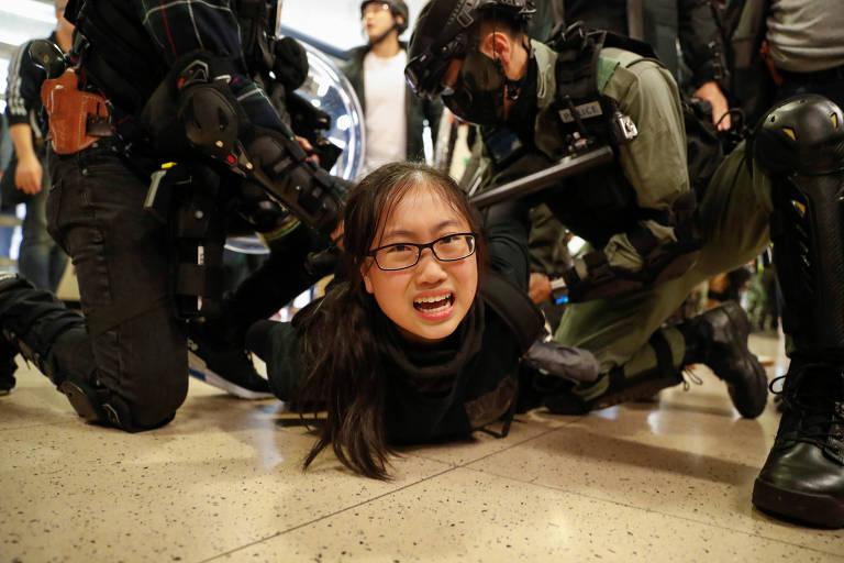 Jovem está no chão, com policiais fardados a segurando. Ela olha para a câmera e tem feições de dor.