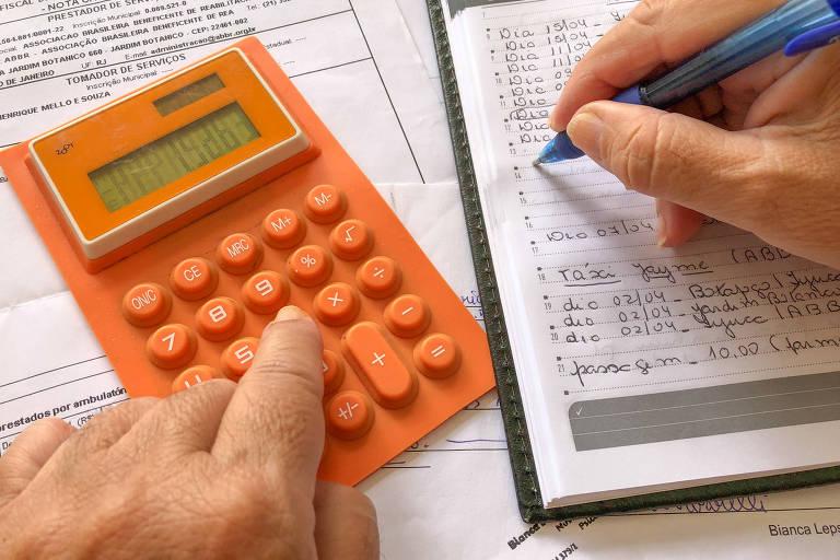 Uma pessoa faz contas em uma calculadora laranja e anota os resultados em um caderno