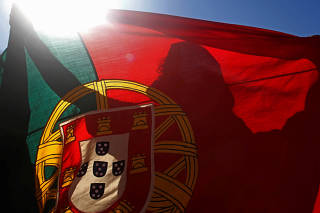 FILE PHOTO: A Portugal fan holds the country's national flag during the team's World Cup soccer match against Ghana at a public screening in Lisbon