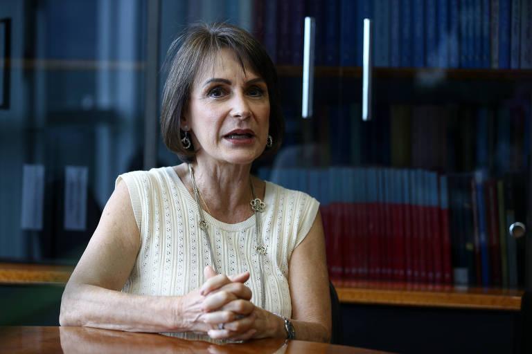Mulher de cabelo curto e usando vestido, sentada, dá entrevista