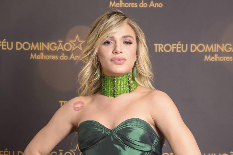 Atriz Glamour Garcia está olhando para frente fazendo biquinho. Ela usa vestido de gala verde musgo e colar de miçangas verde