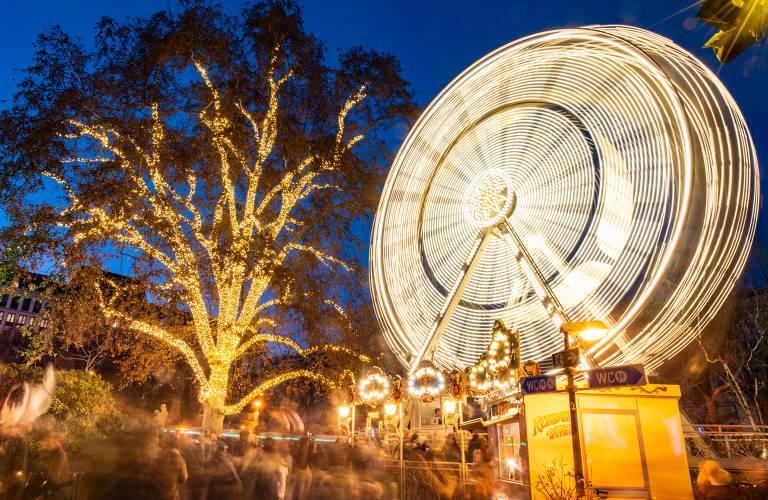 Na imagem, há uma grande árvore ao lado de uma roda gigante no mercado Rathausplatz, em Viena, na Áustria. Ambas estão iluminadas para o Natal.
