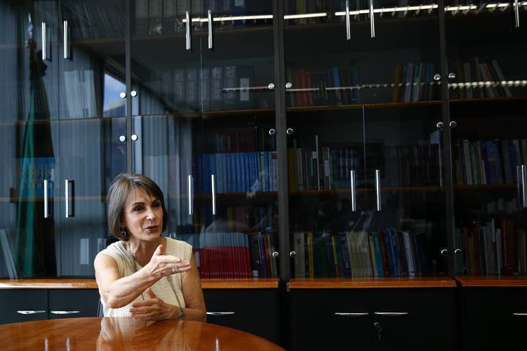 Maria Cristina Peduzzi veste uma peça de roupa off white e gesticula a mão, como se estivesse argumentando. Ela esta no canto inferior esquerdo da imagem. Atrás, está uma estante cheia de livros