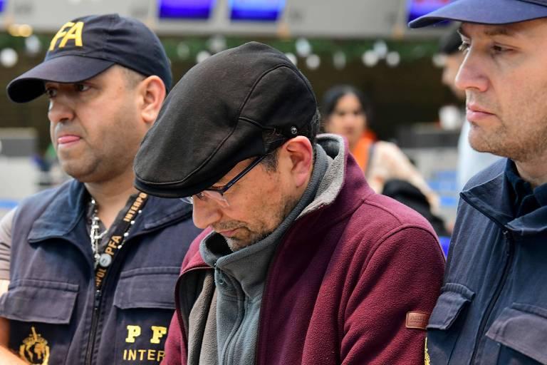O ex-agente argentino Mario Sandoval é escoltado por policiais na chegada ao aeroporto em Buenos Aires