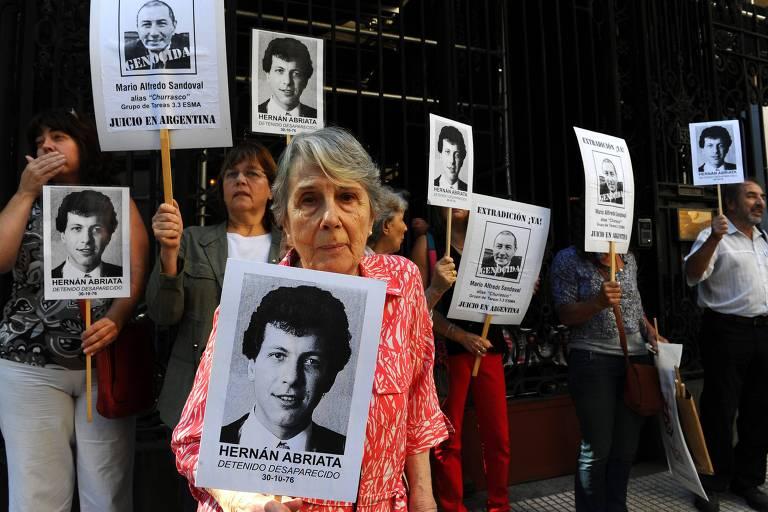 Em abril de 2014, Beatriz Cantarini de Abriata, mãe de Hernan Abriata, segura uma foto de seu filho em frente à embaixada da França, em Buenos Aires