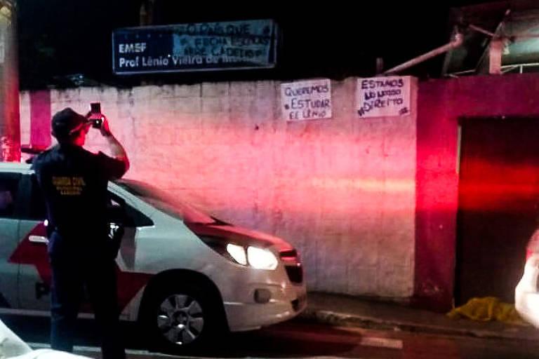 """Na imagem mostra a fachada do colégio Lenio Vieira de Moraes Professor, em Barueri (SP). Do lado esquerdo há uma viatura da polícia e um policial em pé. Do lado direito há cartazes dos estudantes que dizem: """"queremos estudar"""" e """"estamos no nosso direito"""""""