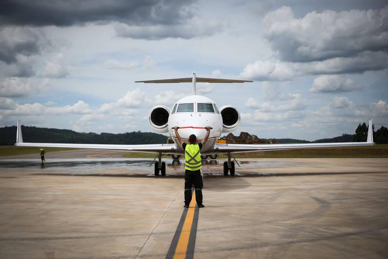 Avião de pequeno porte centralizado em uma pista de pouso/decolagem; um funcionário vestindo um colete sinalizador observa e orienta o avião