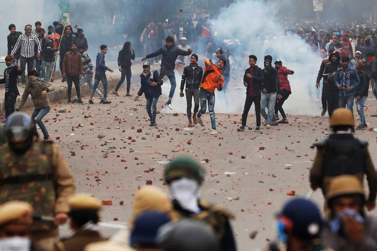 Manifestantes jogam pedras contra a polícia durante protesto contra a nova lei de cidadania, em Déli