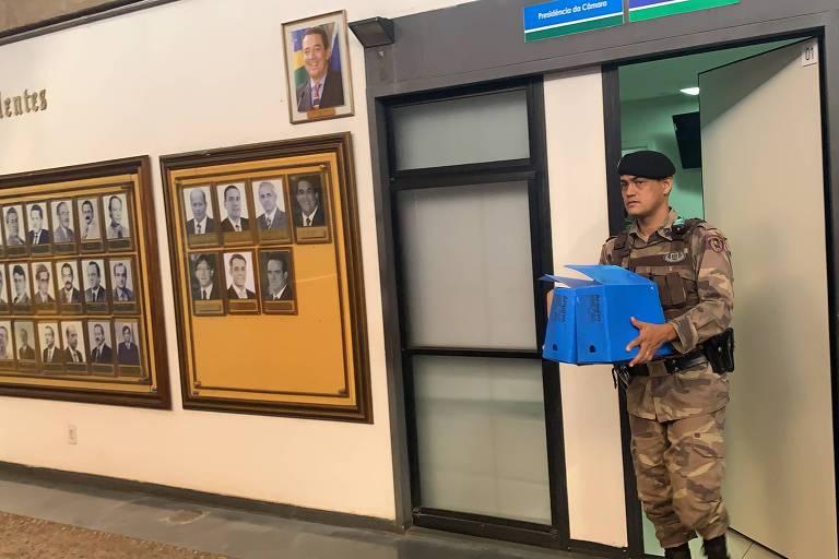 Homem fardado carrega caixa azul em corredor com laterais repletas de fotos