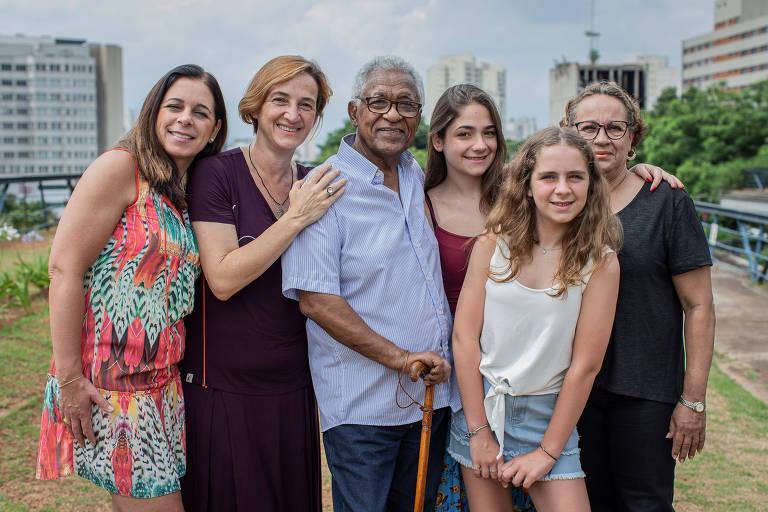 Retrato do venezuelano Raul Escalona e sua mulher, Elvira Barroso (de preto), com sua família brasileira; todos abraçados olhando para a câmera