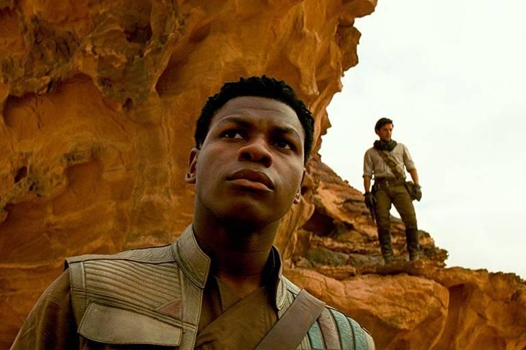Homem negro olha para cima em cenário desértico