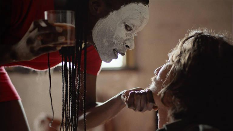 Mulher negra com rosto pintado de branco segura queixo de um homem