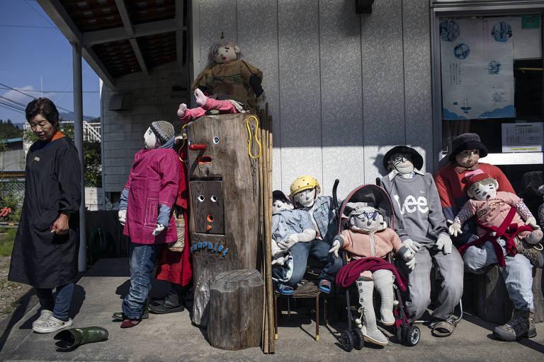 Criadora dos bonecos, Tsukimi Ayano ao lado de algumas de suas obras em Nagoro, no Japão